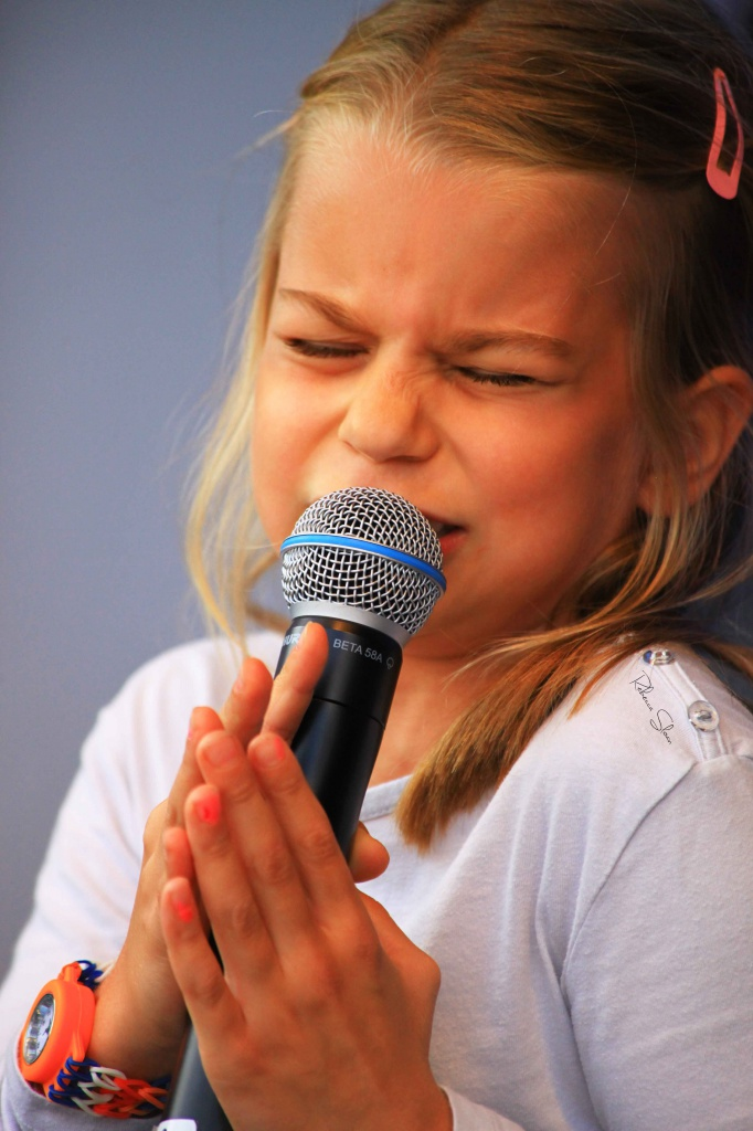 A little girl sings into a microphone